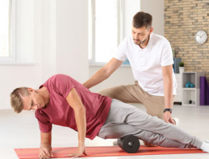 Male trainer helping male client stretch outside leg muscles